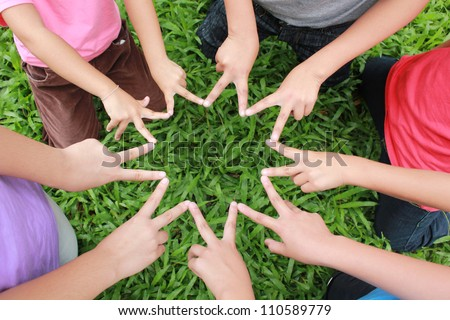 Children hands with green grass background. - stock photo