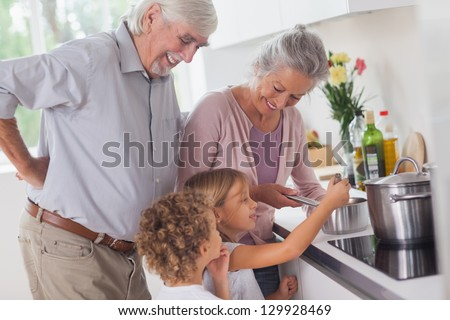 Children happily cooking with grandparents in kitchen - stock photo