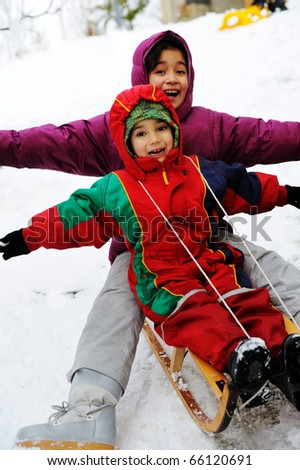children have fun together sliding downhill on a pleasant winter day - stock photo