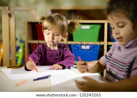 Children having fun at school, two happy young girls drawing in kindergarten