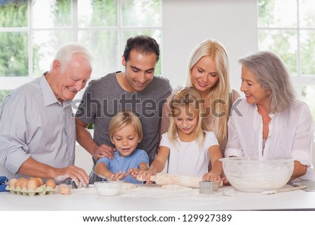 Children having fun baking with family watching them - stock photo