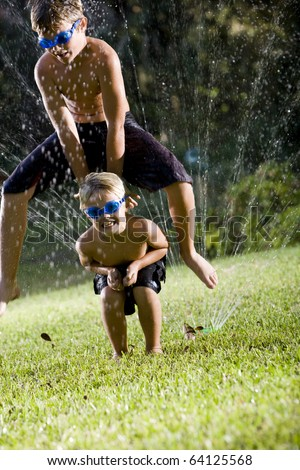 Children having fun getting wet and playing leapfrog, ages 7 and 9 - stock photo
