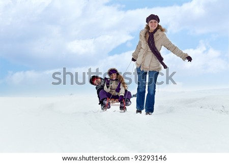 Children having fun on a sleigh in the snow with their mother - stock photo