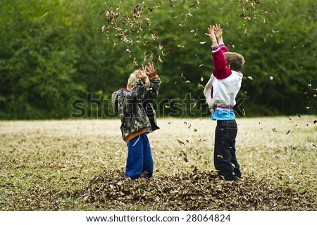 Children having leaf wars in the fall - stock photo