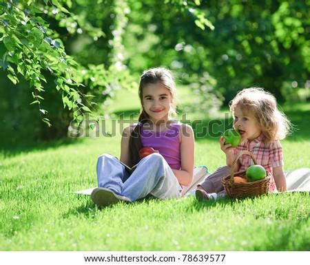 Children having picnic in summer park - stock photo