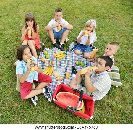 Children having picnic on meadow in circle - stock photo