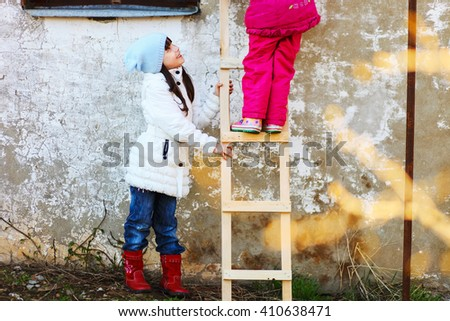 Children help each other to climb the ladder. - stock photo