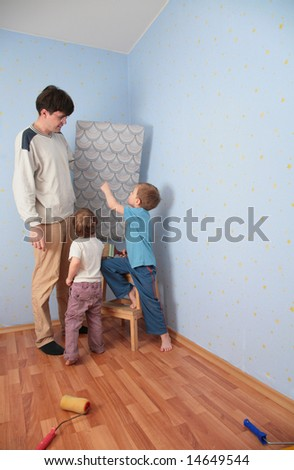 Children help father to glue wall-papers