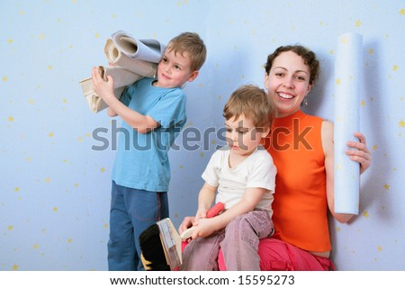 Children help mothrer to glue wall-papers - stock photo