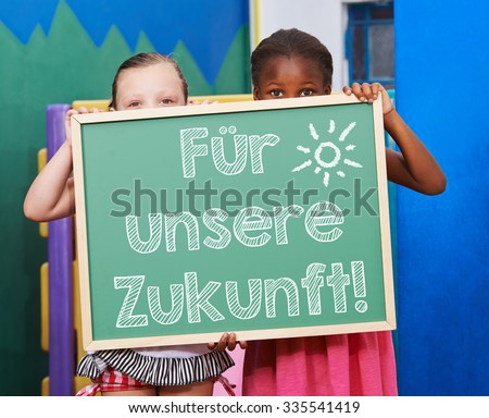 """Children holding chalkboard with German slogan """"Fuer unsere Zukunft"""" (For our future) - stock photo"""