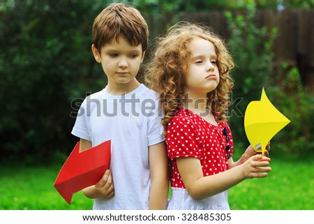 Children holding color arrow pointing right and left, in summer park. Childhood, frendship concept. - stock photo