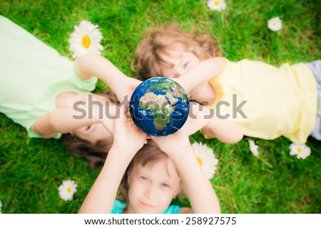 Children holding 3D planet in hands against green spring background. Earth day holiday concept. Elements of this image furnished by NASA - stock photo