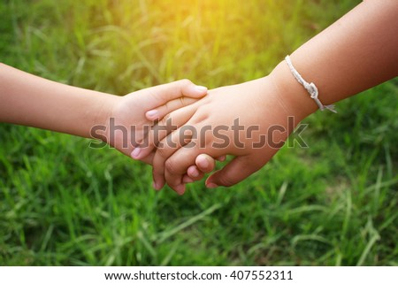 Children holding hands on the green grass with the sunlight