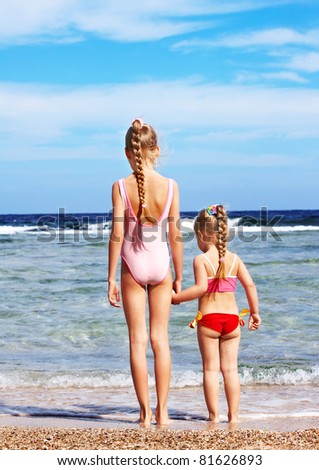 Children holding hands walking on the beach. Rear view. - stock photo