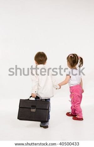 Children holding hands, walking with briefcase. isolated - stock photo
