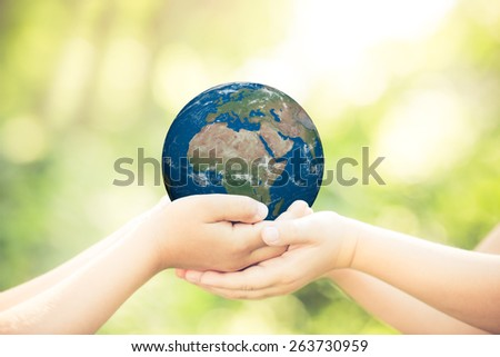 Children holding planet in hands against green spring background. Earth day holiday concept. Elements of this image furnished by NASA - stock photo