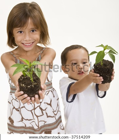 Children holding young plants ready for planting. - stock photo