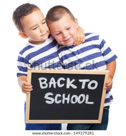 children hugging and holding a blackboard on a white background - stock photo