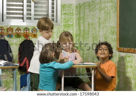 Children in a classroom.  They are working together.  Horizontally framed shot. - stock photo