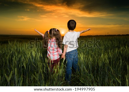 children in a field at sunset - stock photo
