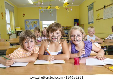 Children in a yellow classroom during a lesson. All are laughing to camera. - stock photo