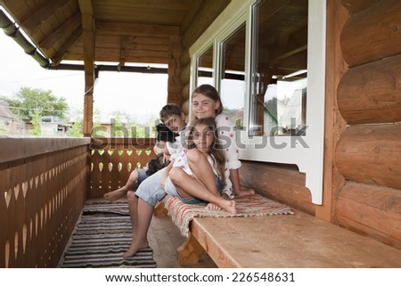 Children in an embroidered shirts sitting on a bench on the balcony - stock photo