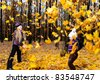 Children in autumn forest. Play fallen down leaf - stock photo