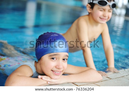 Children  in blue water of the swimming pool, summer time for fun - stock photo