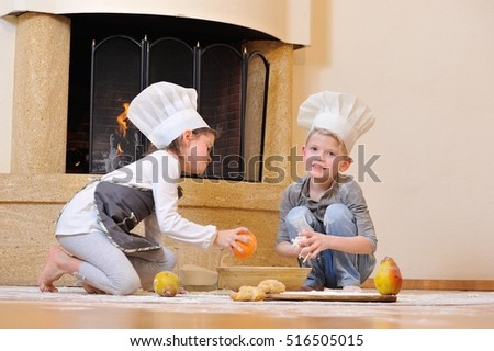 Children in chef's hats near the fireplace: girl dressed in a toque sitting on the kitchen floor and playing cook with her blue eyed cousin, theyâ??re totally stained with flour