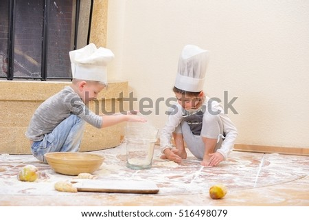 Children in chef's hats near the fireplace: pretty 6 years old girl dressed in a toque sitting and playing cook with her blue eyed cousin, they are totally stained with flour