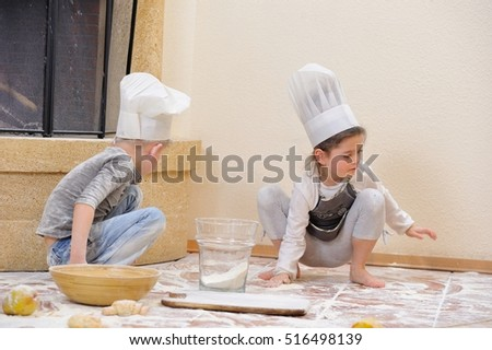 Children in chef's hats near the fireplace: pretty 6 years old girl dressed in a toque sitting and playing cook with her cousin, they are totally stained with flour