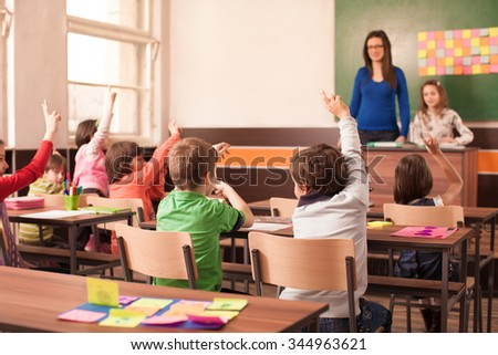 Children in elementary school are raised hand in classroom. Teacher is in the background in front of chalkboard. - stock photo