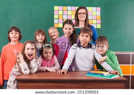 Children in elementary school posing with their teacher in front of chalkboard - stock photo