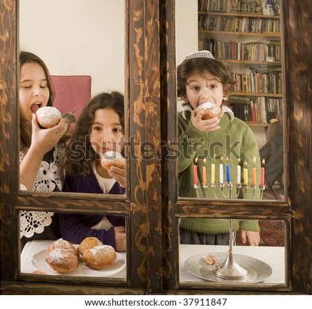 children in front of a Hanukkia eating traditional jelly doughnut in Hanukka - stock photo