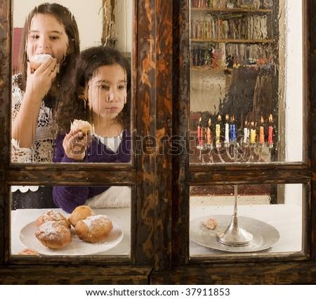 children in front of a Hanukkia eating traditional jelly doughnut in Hanukka - stock photo