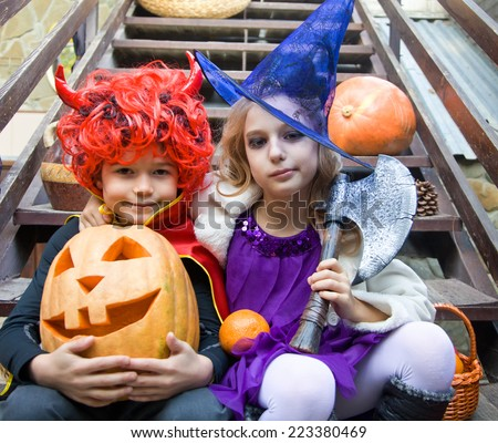 children in halloween costumes with pumpkin fooled on holiday - stock photo