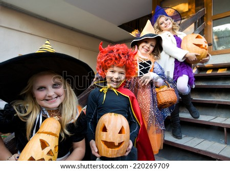 children in halloween costumes with pumpkin walk in guests - stock photo