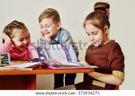 children in kindergarten reading books and laughing