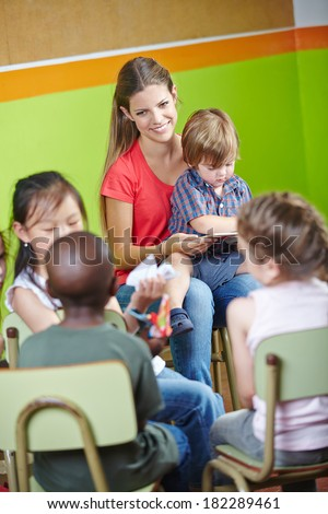 Children in kindergarten sitting in circle and reading book with nursery teacher - stock photo