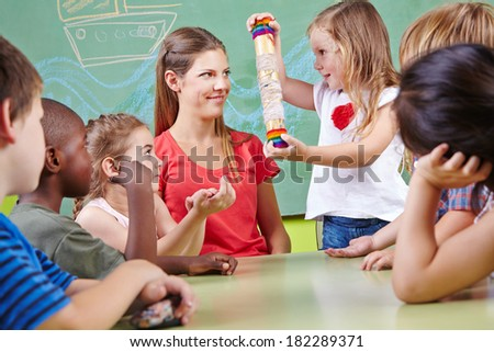 Children in musical education in kindergarten playing with rainmaker instrument - stock photo