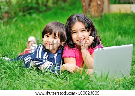 Children in nature with laptop - stock photo
