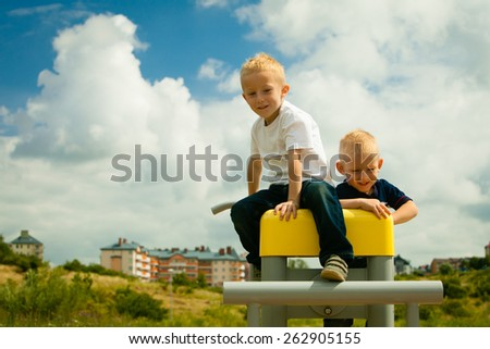 Children in playground kids in action boys playing on leisure equipment climbing outdoors - stock photo