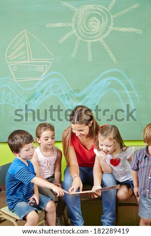 Children in preschool reading book together with a nursery teacher - stock photo