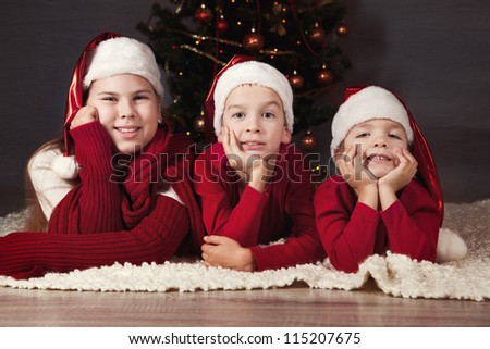 children in red hats are around Christmas tree. - stock photo