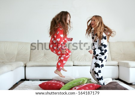 Children in soft warm pajamas playing at home - stock photo