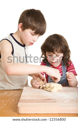 children in the kitchen making a dough - stock photo