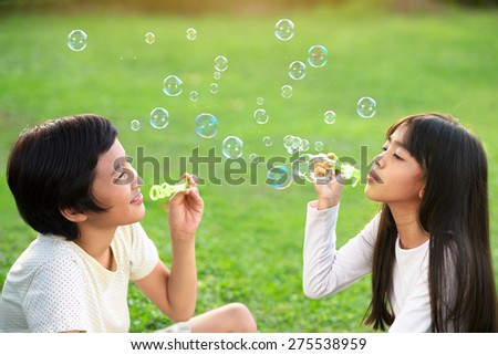Children in the park blowing soap bubbles - stock photo