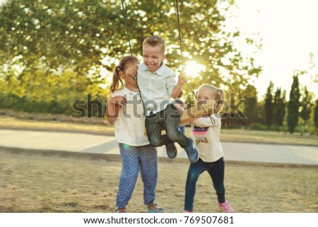 children in the park, happy boy on the swing