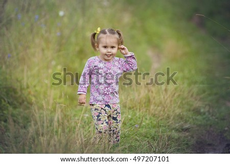 Children in the village walk in the tall grass