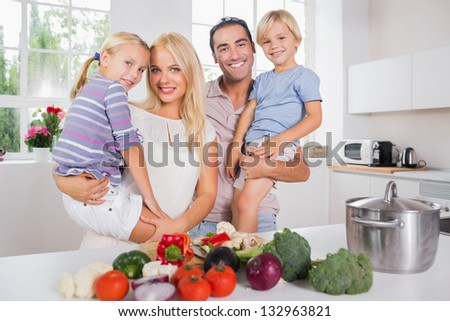 Children in their parents arms in the kitchen preparing vegetables - stock photo